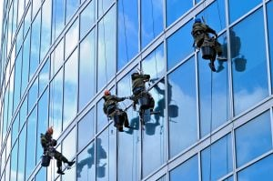 Industrial climbers are washing glass on the facade of a skyscrape